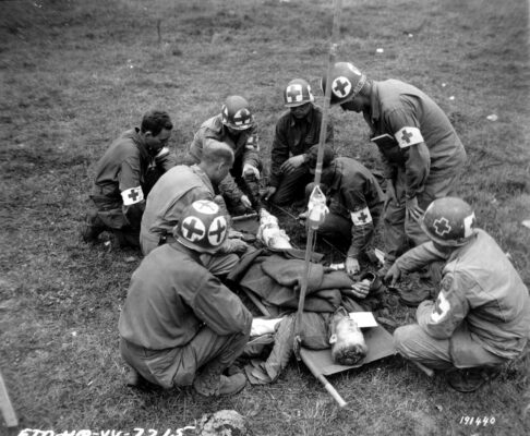 WWII medics provide care to a wounded soldier